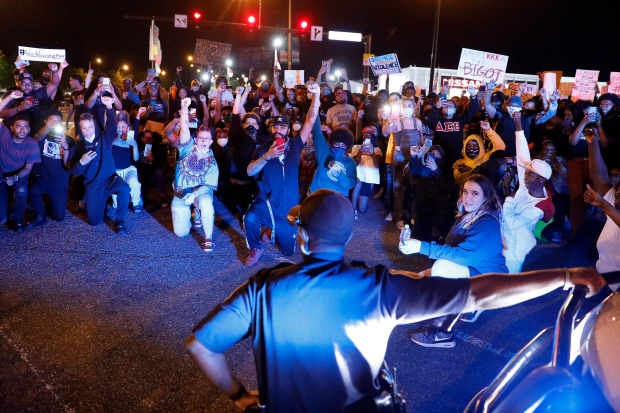 In this Tuesday, June 2, 2020 photo, protesters cheer as a Hampton police officer kneels with them along Mercury Boulevard in Hampton, Va., during a rally against police brutality sparked by the death of George Floyd, a black man who died after being restrained by Minneapolis police officers on May 25. ( Jonathon Gruenke/The Virginian-Pilot via AP)