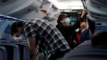 Travelers wear masks for protection from the coronavirus as they settle into their seats on a Delta Airlines flight before takeoff from Ronald Reagan Washington National Airport, Thursday, May 28, 2020, in Arlington, Va. (AP Photo/Julio Cortez)
