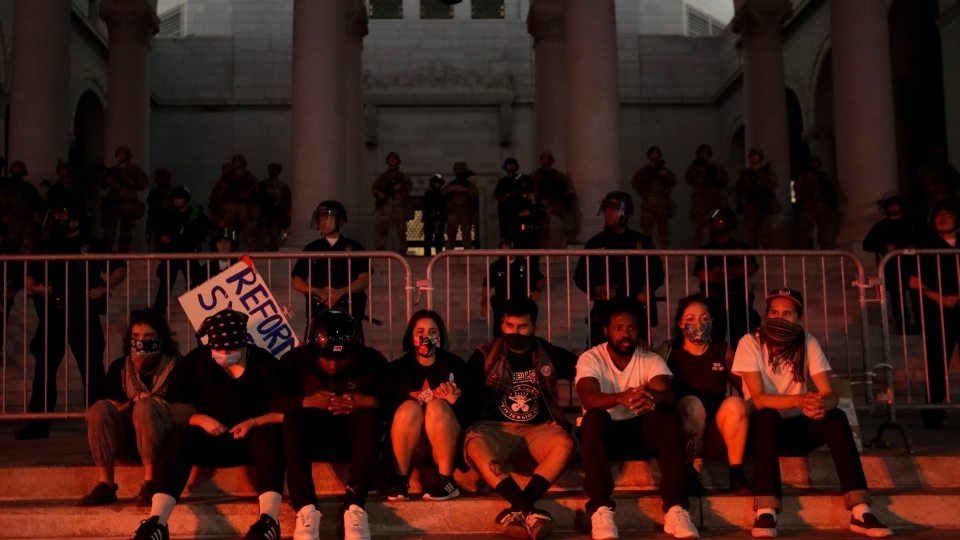 Demonstrators huddle in front of police in front of City Hall shortly before being arrested for a curfew violation Wednesday, June 3, 2020 in downtown Los Angeles during a protest over the death of George Floyd who died May 25 after he was restrained by Minneapolis police. (AP Photo/Marcio Jose Sanchez)