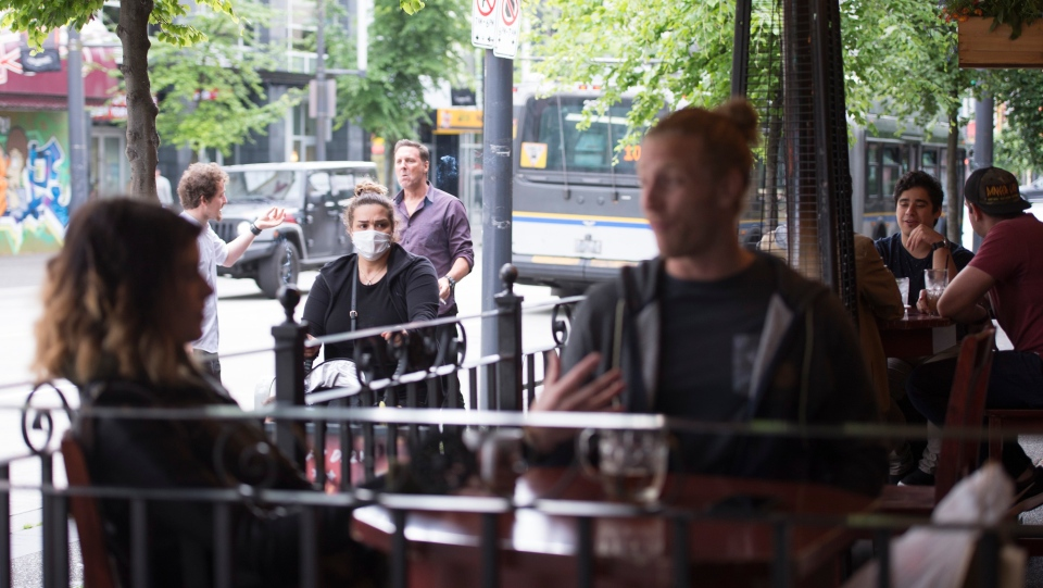 A woman wears a protective face mask as she walks past a opened restaurant patio on Granville Street in Vancouver, Wednesday, May 20, 2020.THE CANADIAN PRESS/Jonathan Hayward