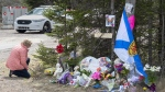 A woman pays her repects at a roadblock in Portapique, N.S. on Wednesday, April 22, 2020. Nova Scotia RCMP are expected to provide an update today on their investigation into the mass killing in April that claimed the lives of 22 victims. THE CANADIAN PRESS/Andrew Vaughan