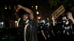 Protesters march down a residential street during a solidarity rally calling for justice over the death of George Floyd, Thursday, June 4, 2020, in the Brooklyn borough of New York. Floyd, an African American man, died on May 25 after a white Minneapolis police officer pressed a knee into his neck for several minutes even after he stopped moving and pleading for air. (AP Photo/Wong Maye-E)