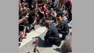 Police Chief Mark Saunders takes a knee with participants at an anti-racism protest in downtown Toronto Friday June 6, 2020. (@marksaunderstps /Twitter)