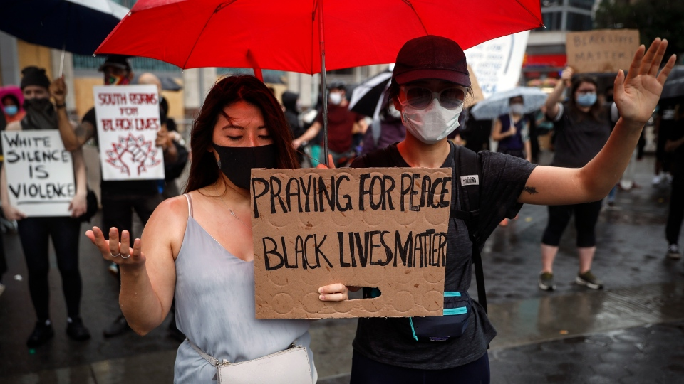 Protesters pray in the rain for a rally at Union Square, Friday, June 5, 2020, in the Manhattan borough of New York. Protests continued following the death of George Floyd, who died after being restrained by Minneapolis police officers on May 25. (AP Photo/John Minchillo)