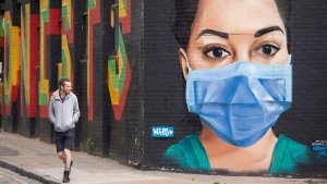 A man views a mural depicting a nurse wearing scrubs and face mask in the Shoreditch area of east London, following the introduction of measures to bring England out of the coronavirus lockdown, Thursday June 4, 2020. Street graffiti has sprung up across the country to highlight the changed times and bravery of front line workers facing the highly contagious COVID-19. (Dominic Lipinski / PA via AP)