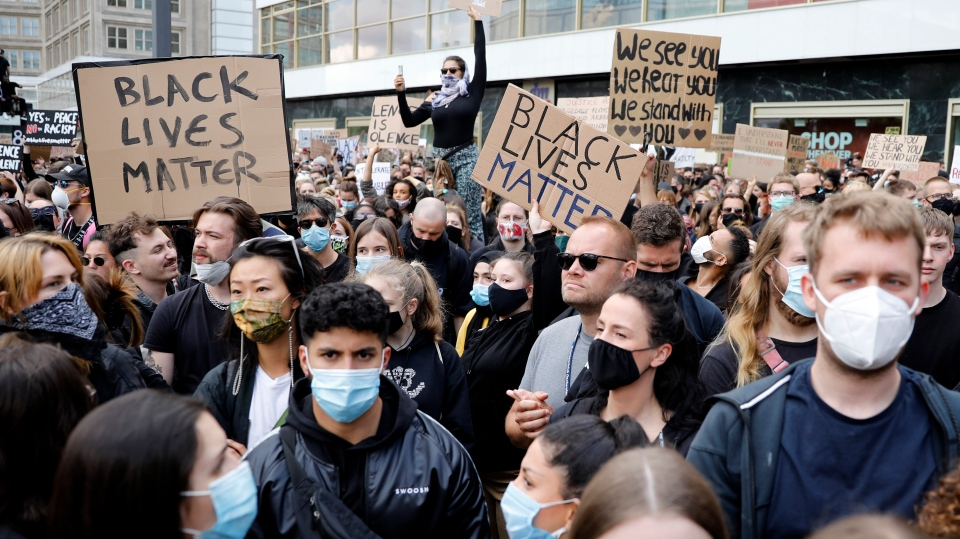 People hold up signs as the gather at the Alexander Platz in Berlin, Germany, Saturday, June 6, 2020, to protest against the recent killing of George Floyd by police officers in Minneapolis, USA, that has led to protests in many countries and across the US. A US police officer has been charged with the death of George Floyd. (AP Photo/Markus Schreiber)