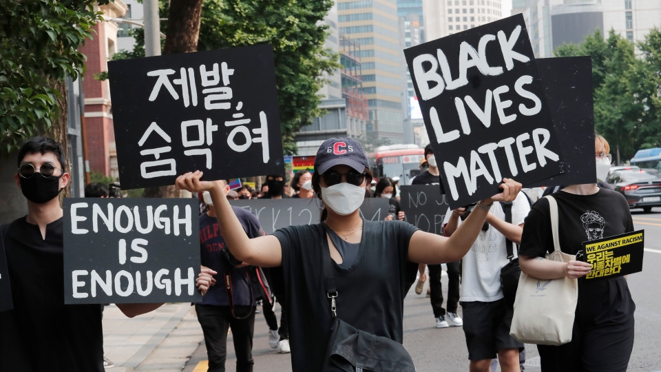 A woman marches to protest during a solidarity rally for the death of George Floyd in Seoul, South Korea, Saturday, June 6, 2020. Floyd died after being restrained by Minneapolis police officers on May 25.(AP Photo/Ahn Young-joon)