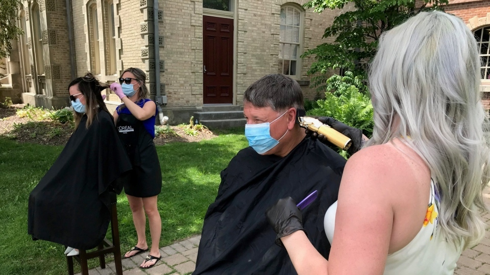 Norfolk County Mayor Kristal Chopp (left) and Haldimand County mayor Ken Hewitt (right) are shown getting hair cuts as a protest against the province's reopening plan on Tuesday. (CTV Kitchener)
