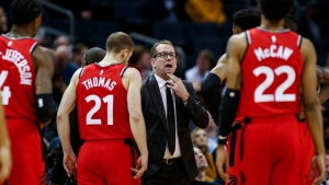 In this Jan. 8, 2020, file photo, Toronto Raptors coach Nick Nurse, center, gathers his team during a timeout in the first half of an NBA basketball game against the Charlotte Hornets in Charlotte, N.C. The Raptors have an NBA championship to defend, a very long stay at the Disney complex awaiting them and plenty of unanswered questions on how the restart of the season will work.  (AP Photo/Nell Redmond, File)