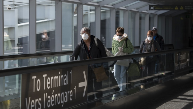 People leave the airport after arriving at Pearson International Airport in Toronto on Monday, March 16, 2020. Flying is about to get even more tedious. Temperature checks. Bigger lines. Fewer meals. No alcohol. And ultimately, higher prices. THE CANADIAN PRESS/Nathan Denette