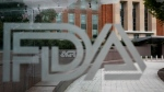 In this Aug. 2, 2018, file photo, the U.S. Food and Drug Administration (FDA) building is visible behind FDA logos at a bus stop on the agency's campus in Silver Spring, Md. (AP Photo/Jacquelyn Martin, File)