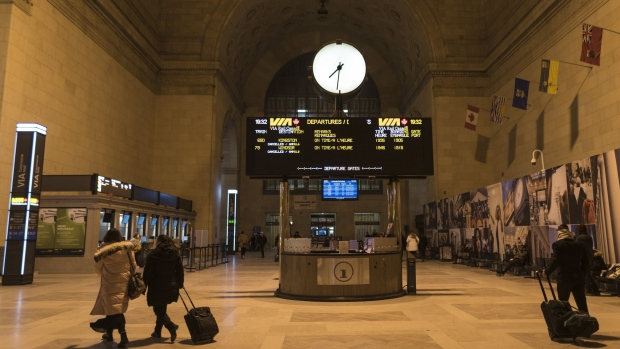 Via Rail says passengers will be required to wear masks as of Tuesday to reduce the risk of spreading COVID-19 when physical distancing can't be maintained. People make their way through Union Station in Toronto as the departure display for Via Rail show all trains have been cancelled on February 13, 2020. THE CANADIAN PRESS/Tijana Martin