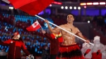 In this Feb. 9, 2018, file photo, Pita Taufatofua carries a flag of Tonga during the opening ceremony of the 2018 Winter Olympics in Pyeongchang, South Korea, Friday, Feb. 9, 2018. Taufatofua decided to leave his shirt on Tuesday, June 23, 2020 when he led a group of 23 fellow Olympians in a home workout video to help celebrate Olympic Day across 20 time zones. (AP Photo/Jae C. Hong, File)