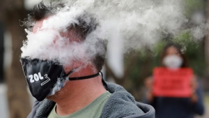 In this June 2, 2020 photo, a demonstrator exhales smoke while wearing a face mask during a protest against the tobacco ban outside parliament in Cape Town, South Africa. (AP Photo/Nardus Engelbrecht)