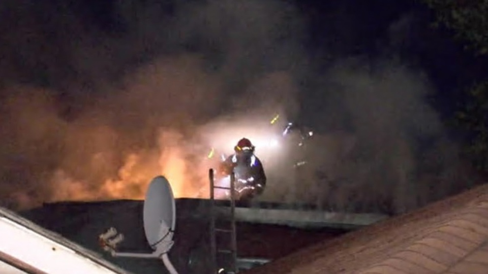 Firefighters are seen on the roof of a burning building on June 29, 2020.