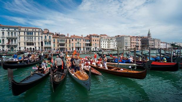 In this Sunday, June 21, 2020 file photo, gondolas are lined up during the Vogada della Rinascita (Rowing of Rebirth) regatta, along Venice canals, Italy. (Anteo Marinoni/LaPresse via AP, File)