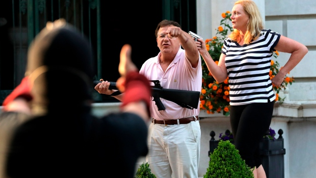Louis couple wave guns at protesters marching past their home