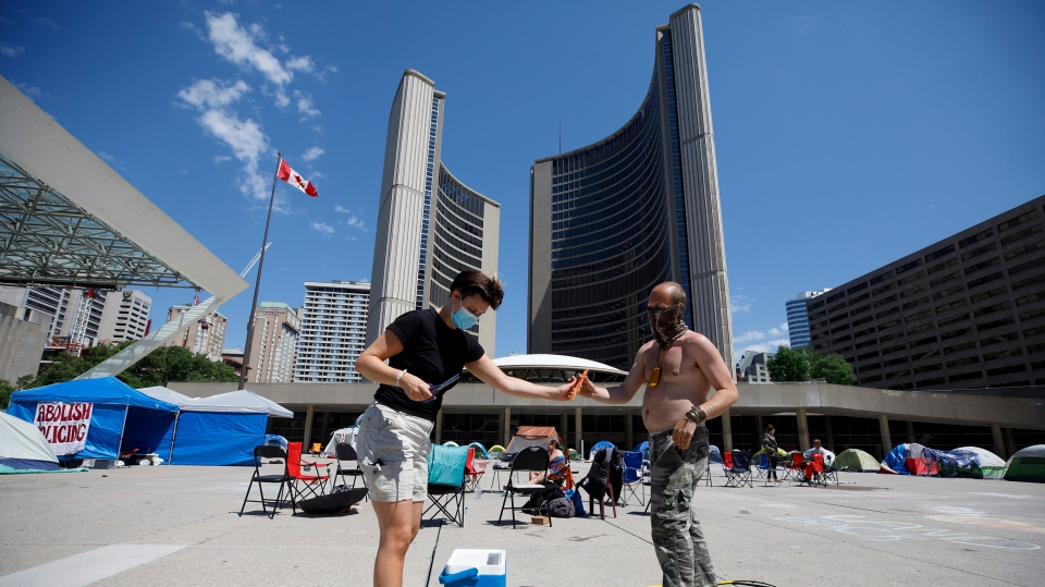A volunteer hands out a frozen treat to Frederick Hillier at an encampment outside of City Hall in Toronto, Friday, June 26, 2020. The group that has set up the tent encampment is calling for the abolishment of police and an end to systemic anti-black anti-indigenous racism in Canada. THE CANADIAN PRESS/Cole Burston
