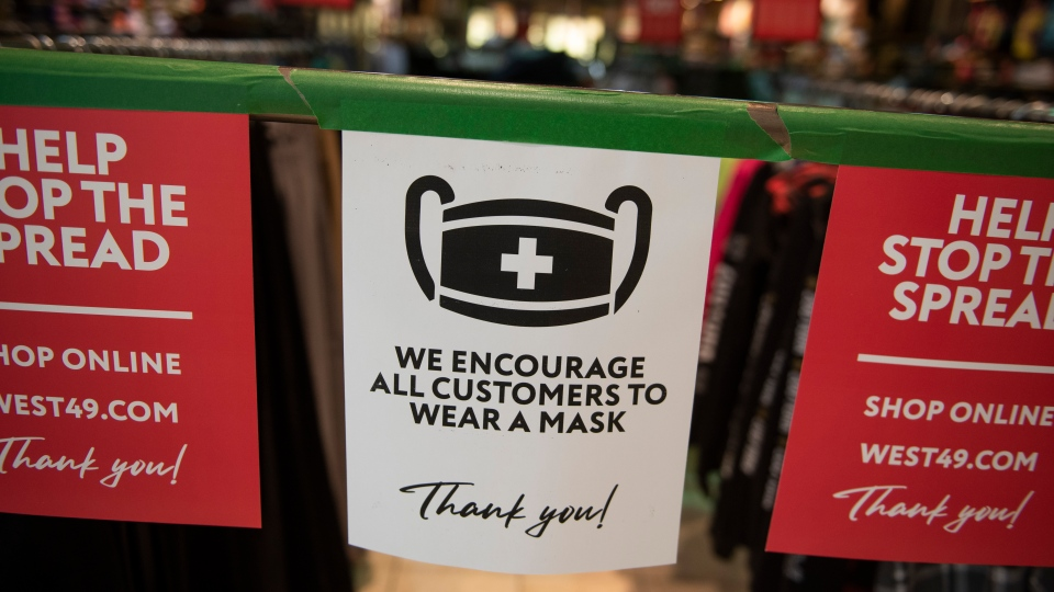 A sign in front of a clothing shop advises customers to wear a mask at the Bayshore Shopping Centre mall in Ottawa, on its first day open as part of Stage 2 of Ontario's plan to lift lockdowns implemented in response to the COVID-19 pandemic, on Friday, June 12, 2020. THE CANADIAN PRESS/Justin Tang