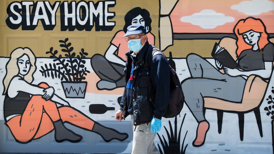 A man wearing a mask walks past a mural made by artist Emily May Rose during the COVID-19 pandemic in Toronto on Friday, May 22, 2020. THE CANADIAN PRESS/Nathan Denette
