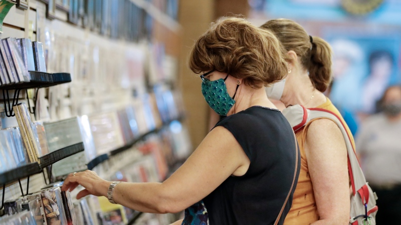 Judy Gallagher, left, wears a mask as she looks through music at the Ernest Tubb Record Shop Monday, June 29, 2020, in Nashville, Tenn. The Nashville Health Department has put in place a mask mandate beginning Monday to help battle the spread of the coronavirus. (AP Photo/Mark Humphrey)