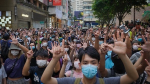 """Protesters against the new national security law march and gesture with five fingers, signifying the """"Five demands - not one less"""" on the anniversary of Hong Kong's handover to China from Britain in Hong Kong, Wednesday, July. 1, 2020. Hong Kong marked the 23rd anniversary of its handover to China in 1997, and just one day after China enacted a national security law that cracks down on protests in the territory. (AP Photo/Vincent Yu)"""