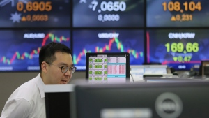 A currency trader watches monitors at the foreign exchange dealing room of the KEB Hana Bank headquarters in Seoul, South Korea, Wednesday, July 1, 2020. Asian shares were higher on Wednesday after Wall Street closed out its best quarter since 1998 with more gains Tuesday but still well below the record high it reached in February. (AP Photo/Ahn Young-joon)