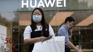 """Residents wearing masks to curb the spread of the coronavirus past by a Huawei shop in Beijing on Friday, June 5, 2020. China on Wednesday demanded Washington stop """"oppressing Chinese companies"""" after U.S. regulators declared telecom equipment suppliers Huawei and ZTE to be national security threats. (AP Photo/Ng Han Guan)"""