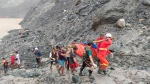 In this photo released from Myanmar Fire Service Department, rescuers carry a recovered body of a victim of a landslide from a jade mining area in Hpakant, Kachine state, northern Myanmar Thursday, July 2, 2020. Myanmar government says a landslide at a jade mine has killed dozens of people (Myanmar Fire Service Department via AP)