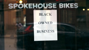 In this Wednesday, June 24, 2020, photograph, a sign in the window informs passersby that Spokehouse Bikes in the Upham's Corner neighborhood of Boston is a Black-owned business. Many from outside Boston have donated to and shopped at the store which was robbed and vandalized earlier in the month. (AP Photo/Charles Krupa)