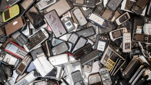 In this photo taken on July 13, 2018, old mobile phones fill a bin at the Out Of Use company warehouse in Beringen, Belgium. The world's mountain of discarded flat-screen TVs, cellphones and other electronic goods grew to a record high last year, according to an annual report released Thursday. (AP Photo/Geert Vanden Wijngaert)