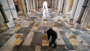 Senior Verger Luke Marshall cleans chairs that have be positioned to allow for social distancing, at Chichester Cathedral as they prepare to reopen for public worship on July 5, as further coronavirus lockdown restrictions are lifted in England, in Chichester, England, Thursday July 2, 2020. (Andrew Matthews/PA via AP)