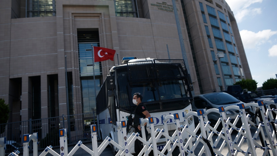 A Turkish police officer guards one of the entrances to a court in Istanbul, Friday, July 3, 2020, where the trial in absentia of two former aides of Saudi Crown Prince Mohammed bin Salman and 18 other Saudi nationals over the 2018 killing of Washington Post columnist Jamal Khashoggi, was scheduled to begin. Turkish prosecutors have indicted the 20 Saudi nationals over Khashoggi's grisly killing at the Saudi Consulate in Istanbul that cast a cloud of suspicion over Prince Mohammed and are seeking life prison terms for defendants who have all left Turkey.Saudi Arabia rejected Turkish demands for the suspects' extradition and put them on trial in Riyadh.(AP Photo/Emrah Gurel)