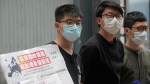 Pro-democracy activists, Joshua Wong, left, Sunny Cheung, center, and Nathan Law holding a placard, speak to media to urge the European leaders against national security law for Hong Kong outside the Legislative Council, in Hong Kong, Wednesday, June 3, 2020. (AP Photo/Kin Cheung)