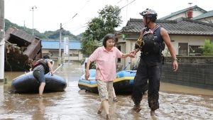 A stranded woman is rescued following a heavy rain in Hitoyoshi, Kumamoto prefecture, southern Japan Saturday, July 4, 2020. Heavy rain in southern Japan triggered flooding and mudslides on Saturday, leaving more than a dozen people presumed dead, some missing and dozens stranded on rooftops waiting to be rescued, officials and news reports said. (Takumi Sato/Kyodo News via AP)