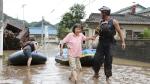 A stranded woman is rescued following heavy rain in Hitoyoshi, Kumamoto prefecture, southern Japan Saturday, July 4, 2020. (Takumi Sato/Kyodo News via AP)