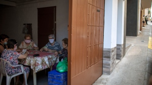 Women play cards inside a house as migrants seeking seasonal work harvesting fruit stand on the street in Fraga, Spain, Thursday, July 2, 2020. Authorities in northeast Spain have ordered the lockdown of a county around the city of Lleida due to worrying outbreaks of the COVID-19 virus. Catalan regional authorities announced Saturday, July 4, 2020 that as of noon local time movement will be restricted to and from the county of El Segriá around Lleida which is home to over 200,000 people. Residents will have until 4 p.m. to enter the area. The new outbreaks are linked to agricultural workers in the rural area. (AP Photo/Emilio Morenatti)