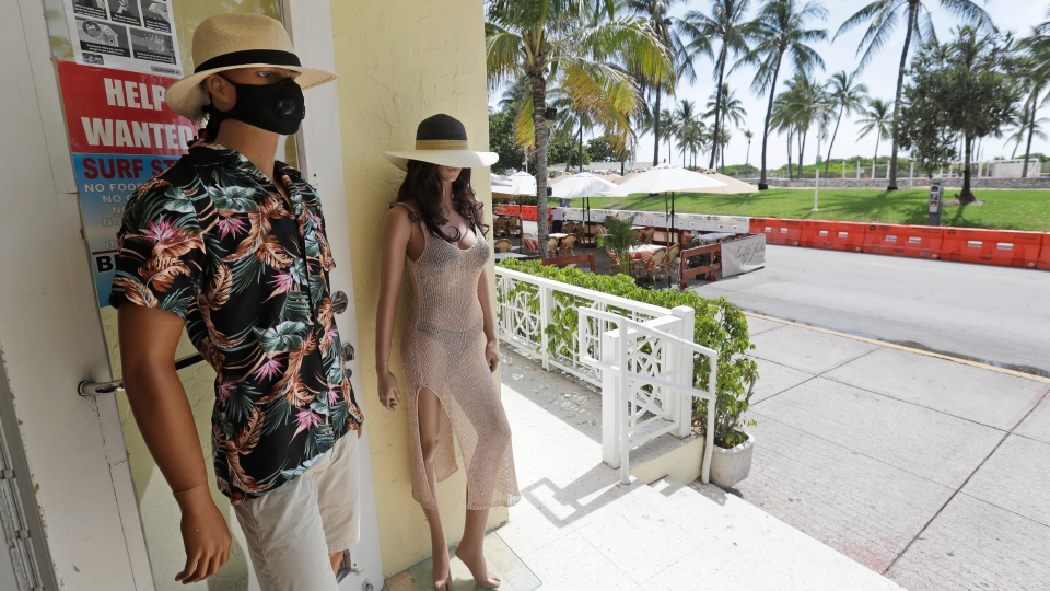 A mannequin wearing a mask is displayed with another outside a store on Miami Beach, Florida's famed Ocean Drive on South Beach, July 4, 2020. The Fourth of July holiday weekend began Saturday with some sobering numbers in the Sunshine State: Florida logged a record number of people testing positive for the coronavirus. (AP Photo/Wilfredo Lee)