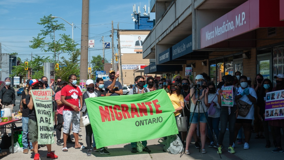 Demonstrators gathered in front of Immigration Minister Marco Mendicino's office in Toronto after the deaths of three migrant workers who contracted COVID-19 to demand full immigration status for all non-permanent residents in Canada in order to extend the benefits of healthcare, emergency income support and labour protections, Saturday, July 4, 2020. THE CANADIAN PRESS/Galit Rodan