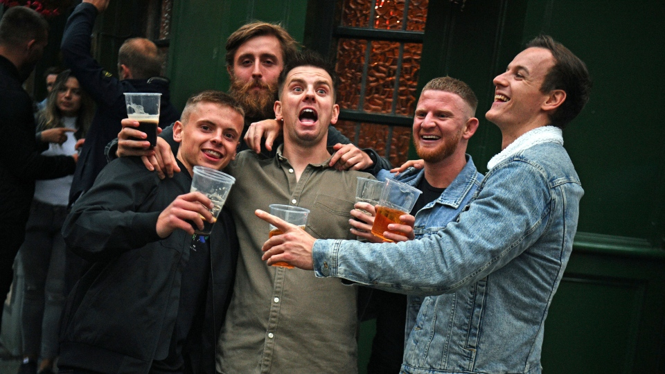 Men pose for a photo, outside a pub as it reopened, in Borough Market, as coronavirus lockdown restrictions eased across the England, in London, Saturday July 4, 2020. England embarked on perhaps its biggest lockdown easing yet as pubs and restaurants reopened for the first time in more than three months. (Victoria Jones/PA via AP)