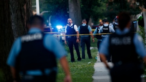 Chicago police officers investigate the scene of a deadly shooting where a 7-year-old girl and a man were fatally shot in Chicago on Sunday, July 5, 2020. At least a dozen people were killed in Chicago over the Fourth of July weekend, police said. Scores of people were shot and wounded. (Armando L. Sanchez/Chicago Tribune via AP)