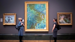 In this Saturday, July 4, 2020 file photo, visitors wearing PPE stand apart as they view Irises, 1914-17, by Claude Monet, a the National Portrait Gallery, London, as it prepares to reopen following the easing of coronavirus lockdown restrictions across England. The British government has announced more than 1.5 billion pounds (almost $2 billion) to help the country's renowned arts and cultural institutions recover from the coronavirus pandemic, after some theaters and music venues warned that without support they might never open again. (Victoria Jones/PA via AP, File)