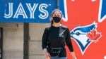 A woman walks past the Toronto Blue Jays logo on the stadium beside the hotel players will stay in if they are allowed to resume training in Toronto on Monday June 29, 2020. THE CANADIAN PRESS/Frank Gunn