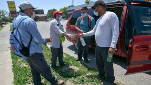 Mexican migrant workers, left to right, Jeremias Cruz, Antonio Dias and Adolfo Gonzalez have their hands sanitized by Juan Silva after the four finished up their month-end banking in Leamington, Ont. on Tuesday, June 30, 2020. THE CANADIAN PRESS/Rob Gurdebeke