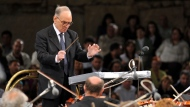 In this July 12, 2009 file photo, Italian composer Ennio Morricone, conducts with the Budapest Symphonic Orchestra - Gyor, performing his best film themes together with the Macedonian Opera Choir, on the opening eve of the 49th Ohrid Summer Festival at the Ancient Theatre in Ohrid, in southwestern Macedonia. (AP Photo/Boris Grdanoski, file)
