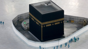 In this March 7, 2020 file photo, workers disinfect the ground around the Kaaba, the cubic building at the Grand Mosque, over fears of the new coronavirus, the Muslim holy city of Mecca, Saudi Arabia. Guidelines were announced Monday, July 6, 2020 as Saudi Arabia gets ready for the 1,000 or so pilgrims that will be allowed to perform the hajj pilgrimage in Mecca later this month. The experience will be unlike any before which usually draws some 2.5 million people. (AP Photo/Amr Nabil, File)