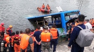Rescuers watch as a bus that fell into a lake is recovered in the Xixiu District of Anshun, southwestern China's Guizhou Province. (Long Rui/Xinhua via AP)