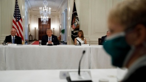 "Sue Ellspermann, right, President of Ivy Tech Community College in Indiana, wears a mask as she listens with President Donald Trump, Vice President Mike Pence, left, and first lady Melania Trump, during a ""National Dialogue on Safely Reopening America's Schools,"" event in the East Room of the White House, Tuesday, July 7, 2020, in Washington. (AP Photo/Alex Brandon)"