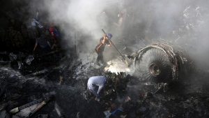 In this May 22, 2020 file photo, volunteers look for survivors of a Pakistan International Airlines plane that crashed in a residential area of Karachi, Pakistan. The spokesman of Pakistan's national carrier said Wednesday, July 8, 2020, that the airline is firing 28 pilots found to have tainted licenses, the latest chapter in a scandal that emerged in the wake of the Airbus A320 crash in Karachi in May. An inquiry into the crash, which killed 97 people on board, resulted in the stunning revelation that 260 of 860 pilots in Pakistan had cheated on their pilots exams, but were still given licences by the Civil Aviation Authority. (AP Photo/Fareed Khan, File)