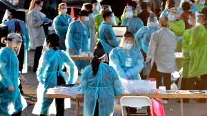 In this June 27, 2020, file photo, medical personnel prepare to test hundreds of people lined up in vehicles in Phoenix's western neighborhood of Maryvalefor free COVID-19 tests organized by Equality Health Foundation, which focuses on care in underserved communities. The personal protective gear that was in dangerously short supply during the initial weeks of the coronavirus crisis in the U.S. is running out again as the virus resumes its rapid spread and the number of hospitalized patients climbs. (AP Photo/Matt York, File)